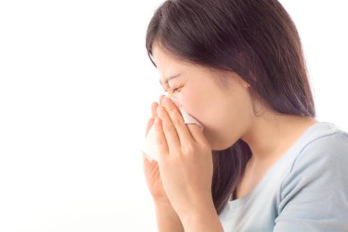 Frau niest wegen Allergie